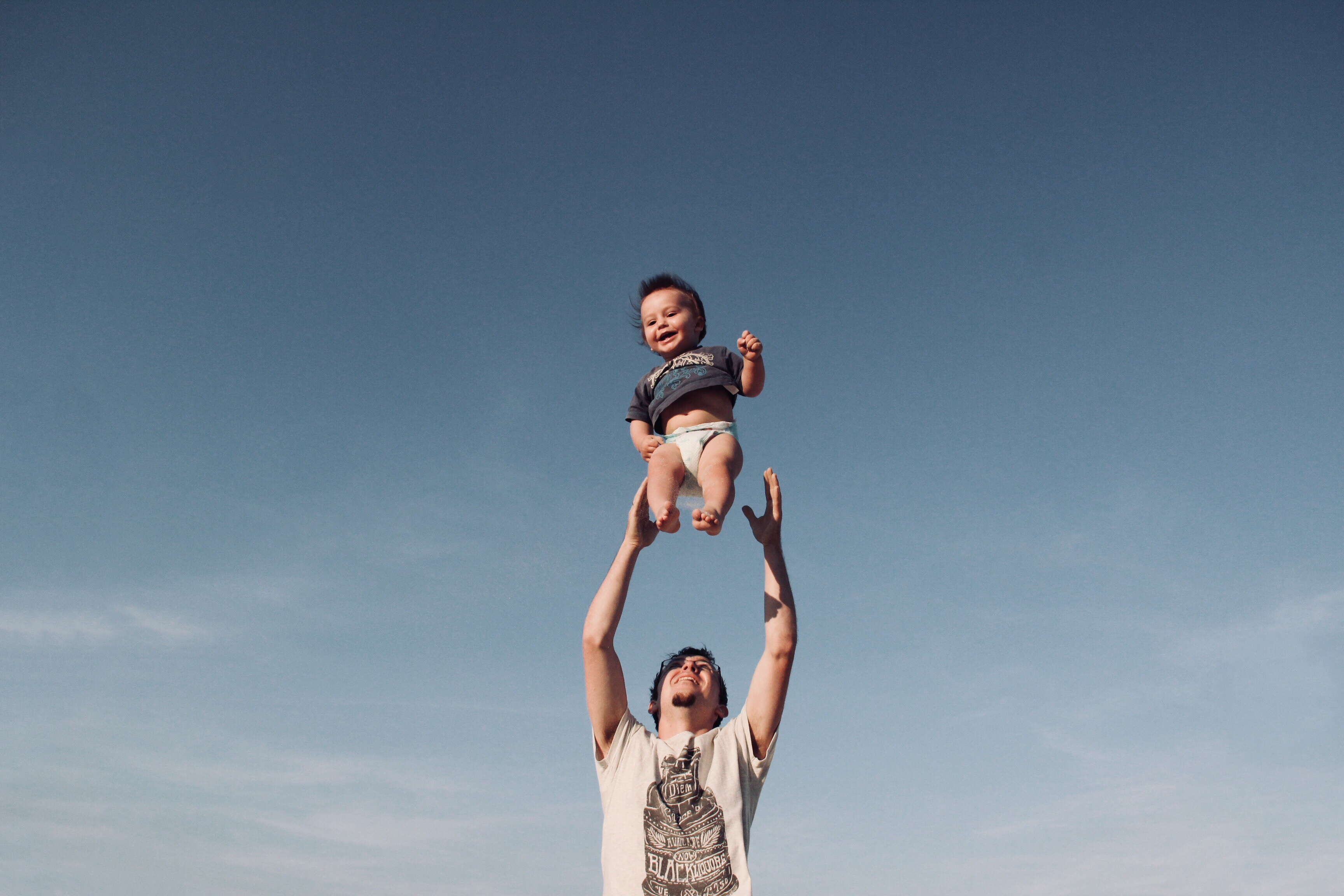 Canva-Photo-of-Man-in-Raising-Baby-Under-Blue-Sky